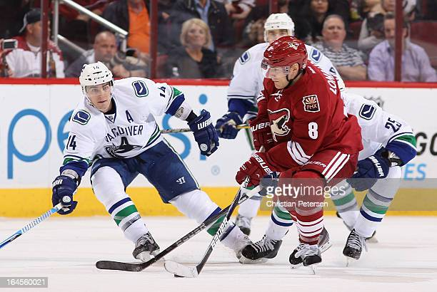 Matthew Lombardi of the Phoenix Coyotes looks to pass the puck pressured by Alex Burrows of the Vancouver Canucks during the NHL game at Jobingcom...