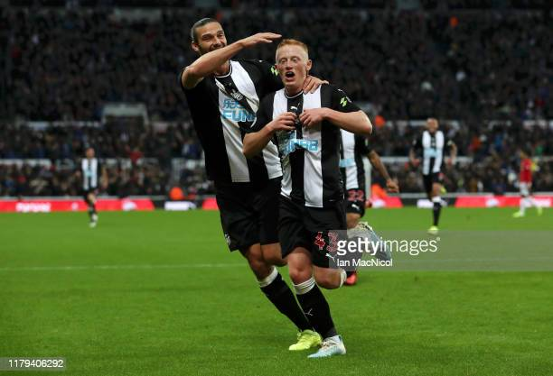 Matthew Longstaff of Newcastle United celebrates with teammate Andy Carroll after scoring his team's first goal during the Premier League match...