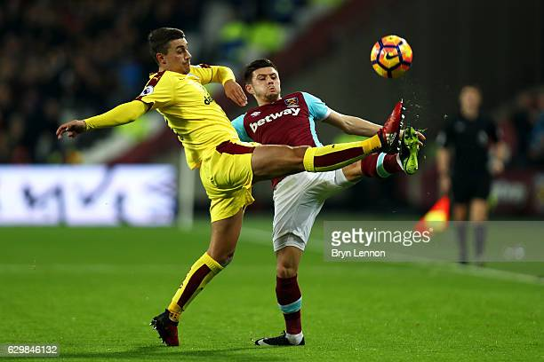 Matthew Lowton of Burnley and Aaron Cresswell of West Ham United battle for possession during the Premier League match between West Ham United and...