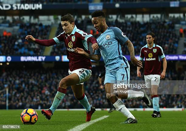 Matthew Lowton of Burnley and Raheem Sterling of Manchester City battle for possession during the Premier League match between Manchester City and...