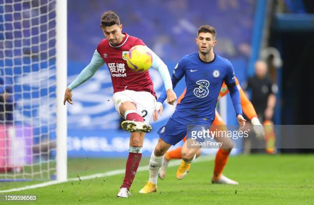 Matthew Lowton of Burnley clears the ball whilst under pressure from Christian Pulisic of Chelsea during the Premier League match between Chelsea and...