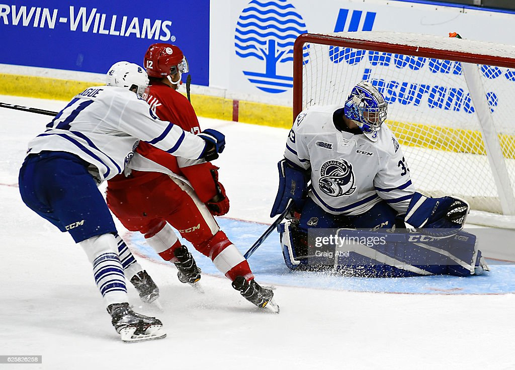 Matthew Mancina #33 makes a glove save on Boris Katchouk #12 of the Sault Ste. Marie Greyhounds as Nicolas Hague #41 defends during game action on November 25, 2016 at Hershey Centre in Mississauga, Ontario, Canada.
