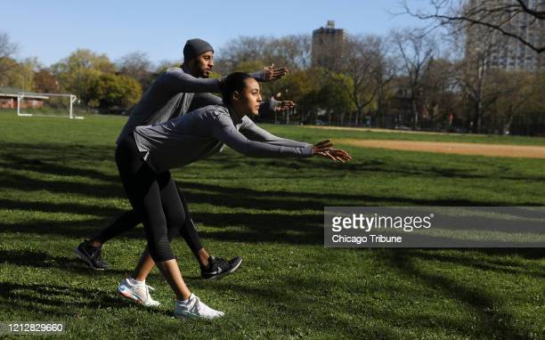 Matthew Manning and his partner Courtney Phillips cofounders of a Chicago running group called GumboFit do light dynamic stretches before their...
