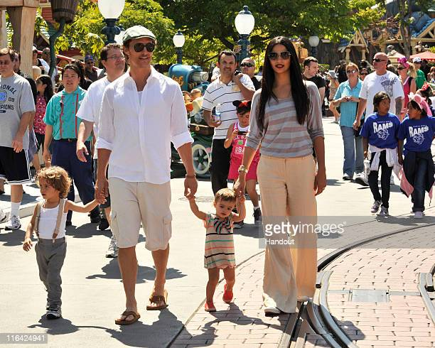 Matthew McConaughey and Camila Alves stroll through Mickey's Toontown with their children son Levi and daughter Vida at Disneyland park on June 15...