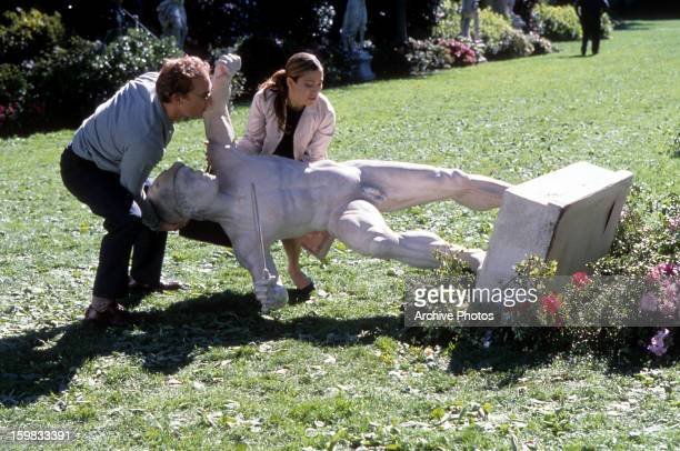 Matthew McConaughey and Jennifer Lopez carry a statue in a scene from the film 'The Wedding Planner' 2001
