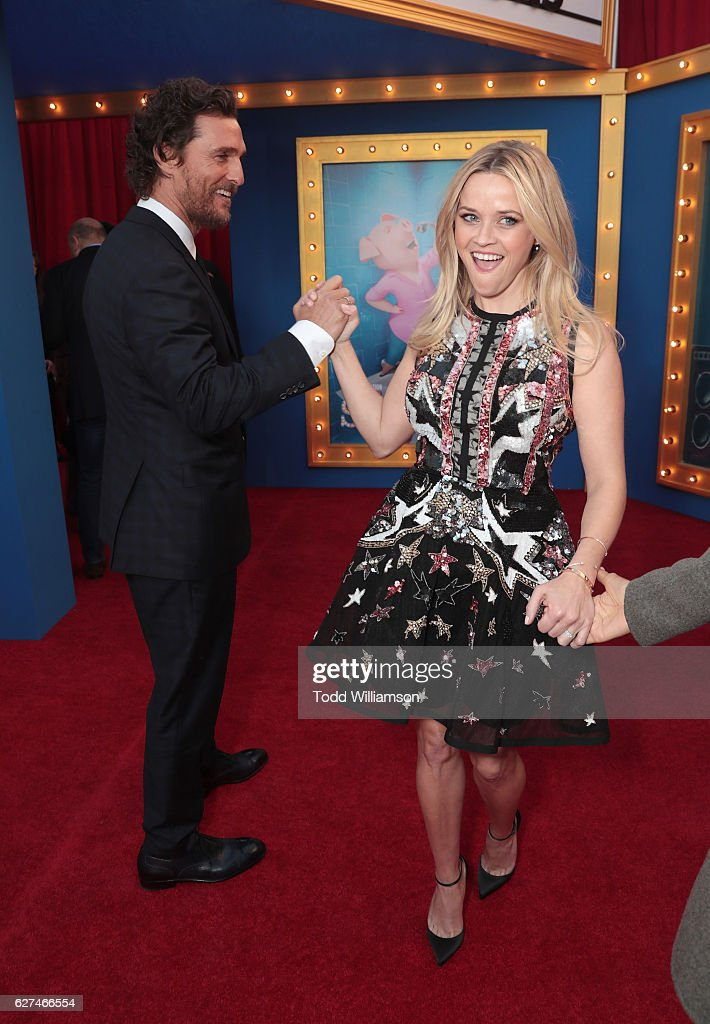 Matthew McConaughey and Reese Witherspoon high five at the premiere Of Universal Pictures' 'Sing' on December 3, 2016 in Los Angeles, California.