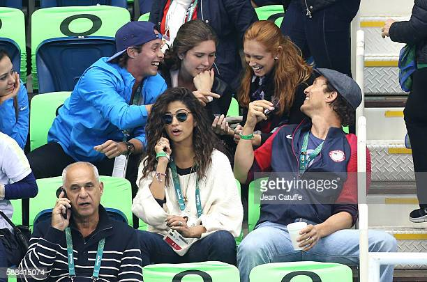 Matthew McConaughey trades pins while his wife Camila Alves is on the phone during the swimming finals on day 5 of the Rio 2016 Olympic Games at...