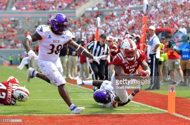 Matthew McKay of the North Carolina State Wolfpack dives past Bruce Bivens and Davondre Robinson of the East Carolina Pirates for a touchdown during...