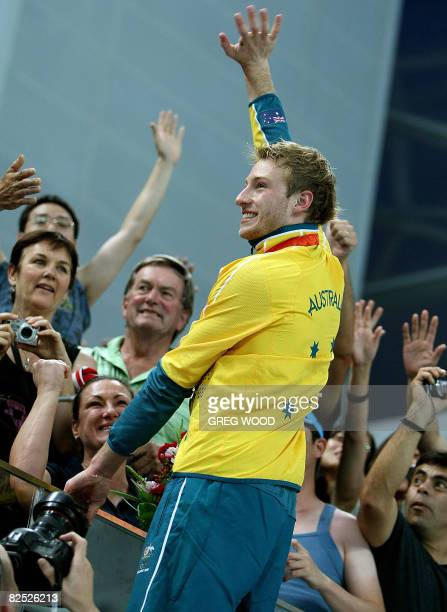 Matthew Mitcham of Australia climbs up near supporters after winning gold for the final of the men's 10m platform diving at the 2008 Beijing Olympic...