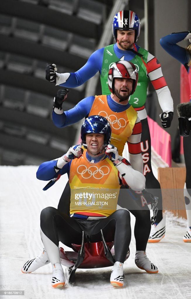 US Matthew Mortensen (bottom), Jayson Terdiman (C) and Chris Mazdzer celebrate after competing in the team relay competition luge final during the Pyeongchang 2018 Winter Olympic Games, at the Olympic Sliding Centre on February 15, 2018 in Pyeongchang. / AFP PHOTO / Mark Ralston