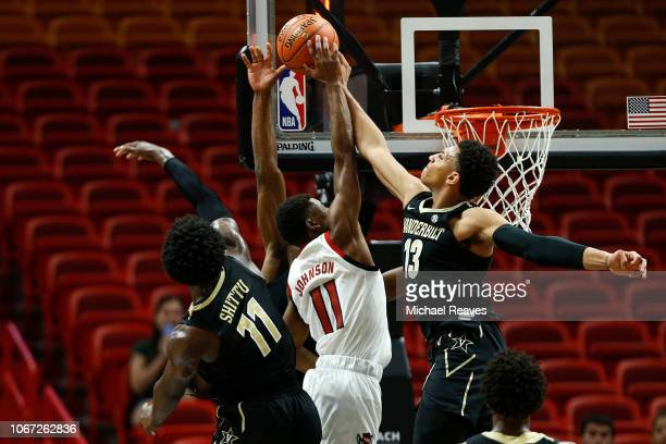 Matthew Moyer and Simisola Shittu of the Vanderbilt Commodores block a shot by Markell Johnson of the North Carolina State Wolfpack during the...