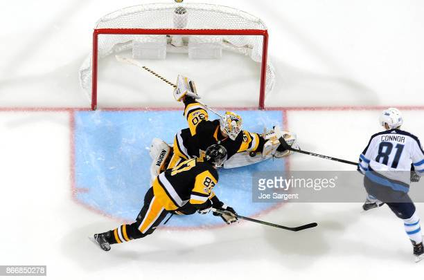 Matthew Murray of the Pittsburgh Penguins makes a save against Kyle Connor of the Winnipeg Jets at PPG Paints Arena on October 26 2017 in Pittsburgh...