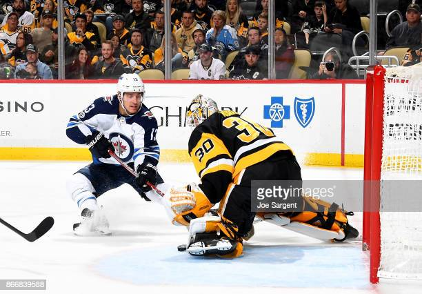 Matthew Murray of the Pittsburgh Penguins makes a save against Brandon Tanev of the Winnipeg Jets at PPG Paints Arena on October 26 2017 in...