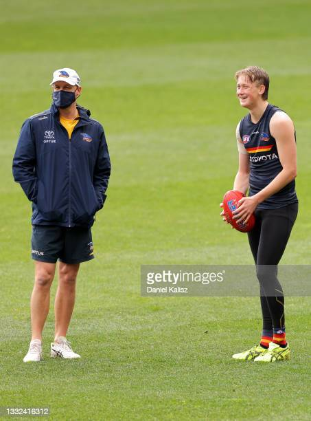 Matthew Nicks, head coach of the Crows talks with Brayden Cook of the Crows during an Adelaide Crows AFL training session at Adelaide Oval on August...