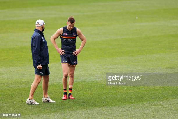 Matthew Nicks, head coach of the Crows talks with Brodie Smith of the Crows during an Adelaide Crows AFL training session at Adelaide Oval on August...