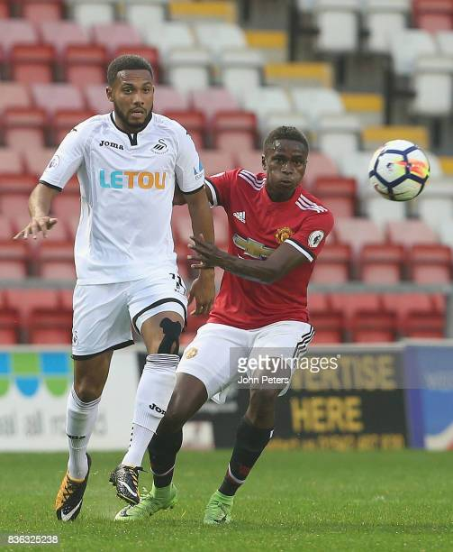 Matthew Olosunde of Manchester United U23s in action with Kenji Gorre of Swansea City during the Premier League 2 match between Manchester United...