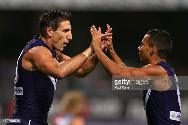 Matthew Pavlich and Danyle Pearce of the Dockers celebrate a goal during the round six AFL match between the Fremantle Dockers and the Essendon...