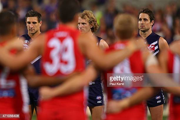 Matthew Pavlich David Mundy and Luke McPharlin of the Dockers look on the pregame ANZAC Day ceremony during the round four AFL match between the...
