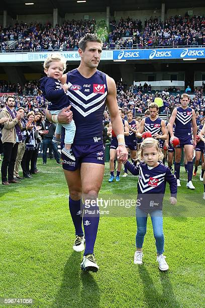 Matthew Pavlich of the Dockers leads his team onto the field with his children Jack and Harper before playing his final game during the round 23 AFL...