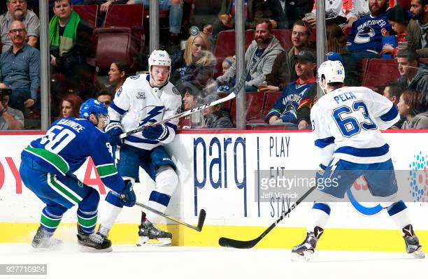 Matthew Peca and Mikhail Sergachev of the Tampa Bay Lightning and Brendan Gaunce of the Vancouver Canucks watch a loose puck during their NHL game at...