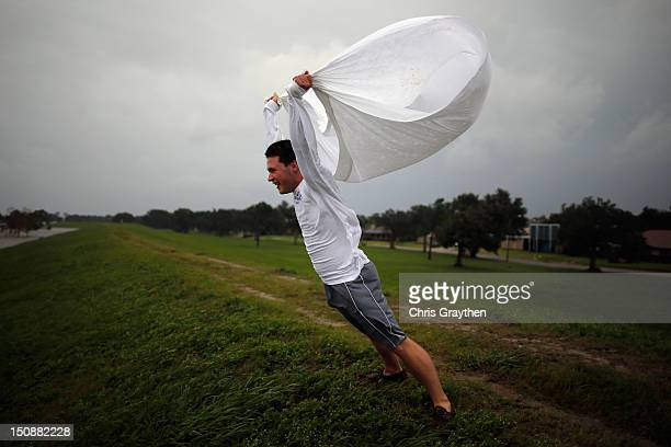 Matthew Pettus holds a sheet open in the wind on the levee near Lake Pontchatrain as Hurricane Isaac approaches on August 28 2012 in New Orleans...