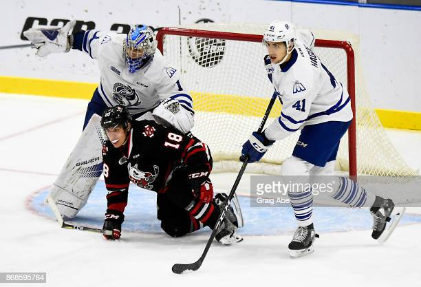 Matthew Philip of the Niagara IceDogs battles for crease space with Jacob Ingham and Nicolas Hague of the Mississauga Steelheads during game action...