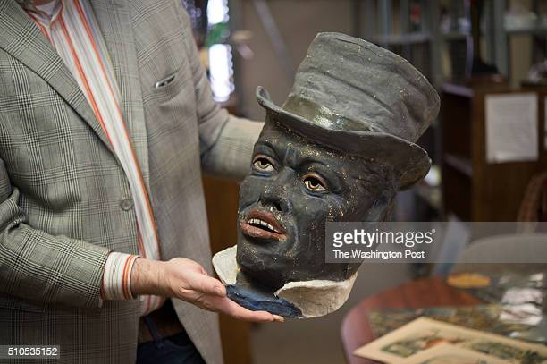 Matthew Quill holds an exceedingly rare late 19th century papiermache Black Minstrel mask possibly made in Paris likely for a Mardi Gras parade float...