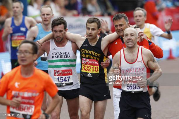 Matthew Rees of Swansea Harriers helps David Wyeth of Chorlton Runners reach the finish line during the London marathon on April 23 2017 in London /...