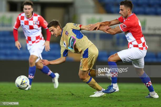 Matthew Ridenton of the Jets and Daniel Dragicevic of the Knights compete for the ball during the FFA Cup round of 32 match between Gold Coast...