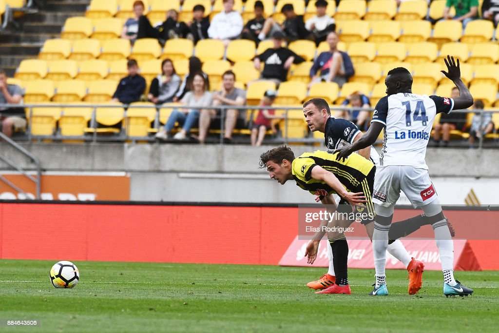 Matthew Ridenton of the Wellington Phoenix tries to get past Thomas Deng and Leigh Broxham of Melbourne Victory during the round nine A-League match between the Wellington Phoenix and the Melbourne Victory at Westpac Stadium on December 3, 2017 in Wellington, New Zealand.