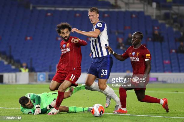 Matthew Ryan of Brighton and Hove Albion collides with Mohamed Salah of Liverpool , Dan Burn of Brighton and Hove Albion and Sadio Mane of Liverpool...