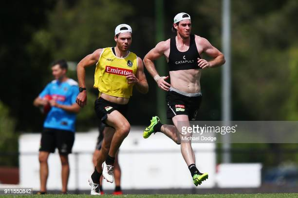 Matthew Scharenberg and Tyson Goldsack sprint during a Collingwood Magpies AFL training session on January 29 2018 in Melbourne Australia