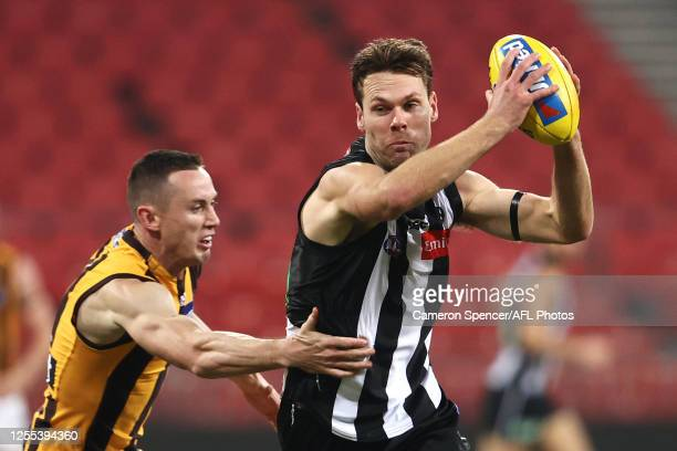 Matthew Scharenberg of the Magpies is tackled by Tom Scully of the Hawks during the round 6 AFL match between the Collingwood Magpies and the...