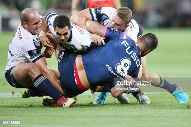 Matthew Scott Justin O'Neill and Coen Hess of the Cowboys tackles Jesse Bromwich of the Storm during the round three NRL match between the Melbourne...