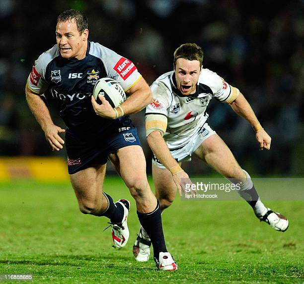 Matthew Scott of the Cowboys breaks the tackle of James Maloney of the Warriors during the round 15 NRL match between the North Queensland Cowboys...