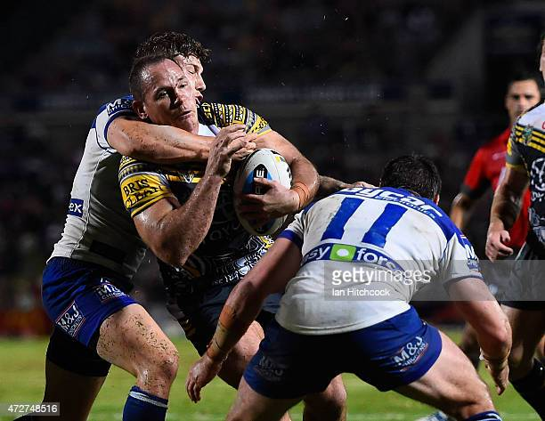 Matthew Scott of the Cowboys is tackled by Joshua Jackson and Trent Hodkinson of the Bulldogs during the round nine NRL match between the North...