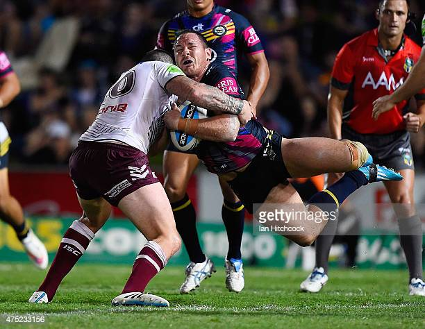 Matthew Scott of the Cowboys is tackled by Luke Burgess of the Sea Eagles during the round 12 NRL match between the North Queensland Cowboys and the...