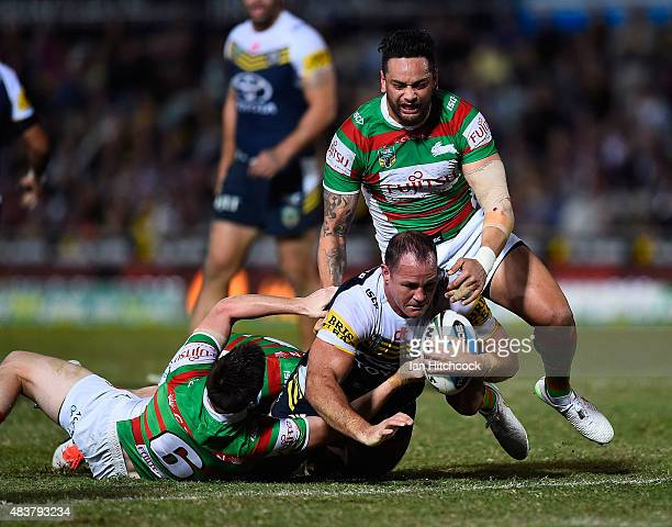 Matthew Scott of the Cowboys is tackled by Luke Keary and John Sutton of the Rabbitohs during the round 23 NRL match between the North Queensland...