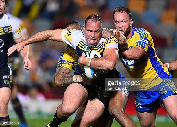 Matthew Scott of the Cowboys is tackled by Manu Ma'u and David Gower of the Eels during the round 20 NRL match between the North Queensland Cowboys...
