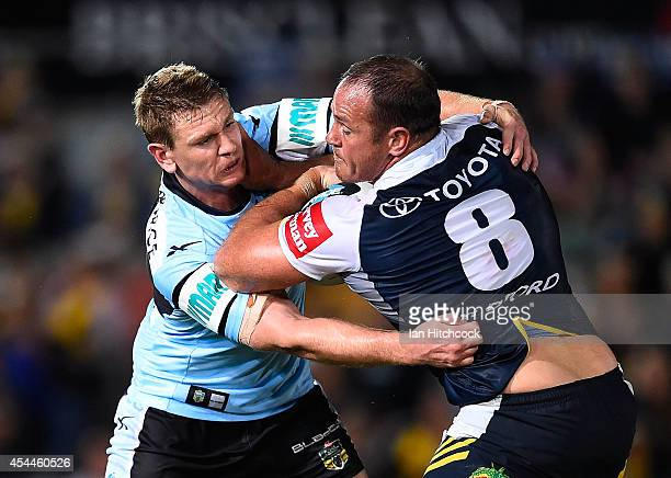 Matthew Scott of the Cowboys is tackled by Tim Robson of the Sharks during the round 25 NRL match between the North Queensland Cowboys and the...