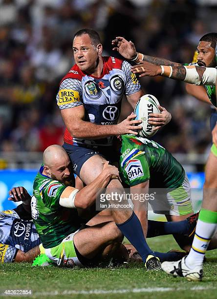 Matthew Scott of the Cowboys looks to off load the ball before he is tackled by Kurt Baptiste of the Raiders during the round 21 NRL match between...