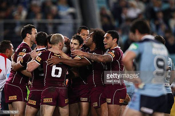 Matthew Scott of the Maroons celebrates with team mates after scoring a try during game three of the ARL State of Origin series between the New South...