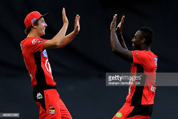 Matthew Short and Andre Russell of the Renegades celebrate after Short caught out Aiden Blizzard of the Thunder from the bowling of Russell during...