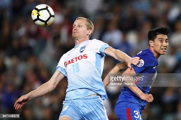 Matthew Simon of Sydney competes with Sun Shilin of Shanghai Shenhua FC during the AFC Champions League match between Sydney FC and Shaghai Shenhua...