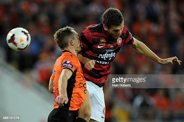 Matthew Smith of the Roar competes for the ball with Matthew Spiranovic of the Wanderers during the 2014 A-League Grand Final match between the...