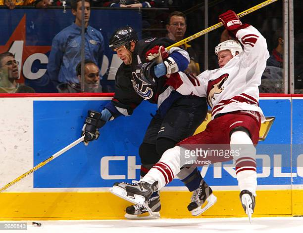 Matthew Spiller of the Phoenix Coyotes takes to the air after being checked by Todd Bertuzzi of the Vancouver Canucks during the second period of...