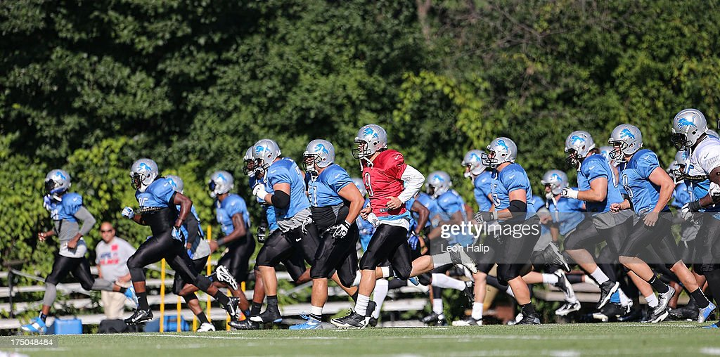 Matthew Stafford #9 of the Detroit Lions leads his team in the morning drills during training camp on July 30, 2013 in Allen Park, Michigan.