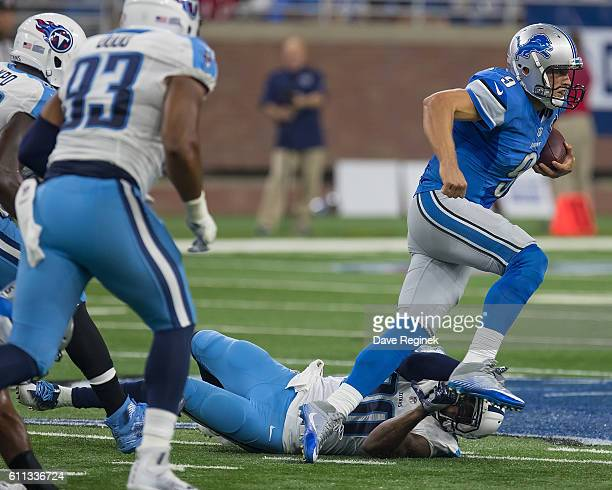 Matthew Stafford of the Detroit Lions runs over Perrish Cox of the Tennessee Titans during an NFL game at Ford Field on September 18 2016 in Detroit...