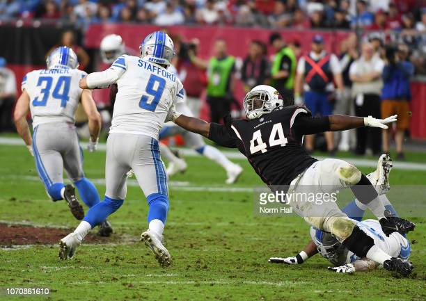 Matthew Stafford of the Detroit Lions runs through a tackle by Markus Golden of the Arizona Cardinals during the first half at State Farm Stadium on...