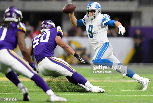 Matthew Stafford of the Detroit Lions runs with the ball while being pursued by Eric Wilson of the Minnesota Vikings in the first half of the game at...